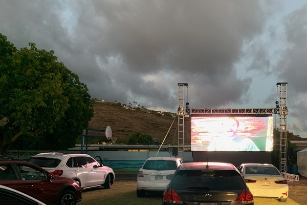 Movie screen at night with cars full of moviegoers