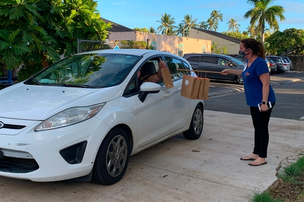 Woman handing goodie bags to white car