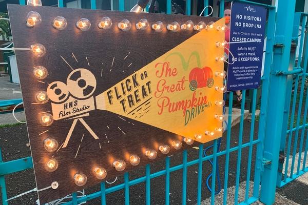 Light up Flick or Treat sign on blue fence